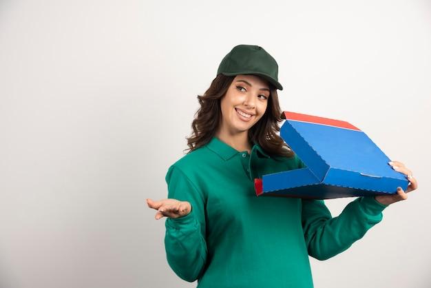 Donna di consegna felice in uniforme verde che tiene la scatola della pizza aperta.