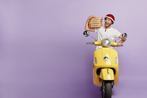 Happy deliveryman driving scooter while holding pizza boxes