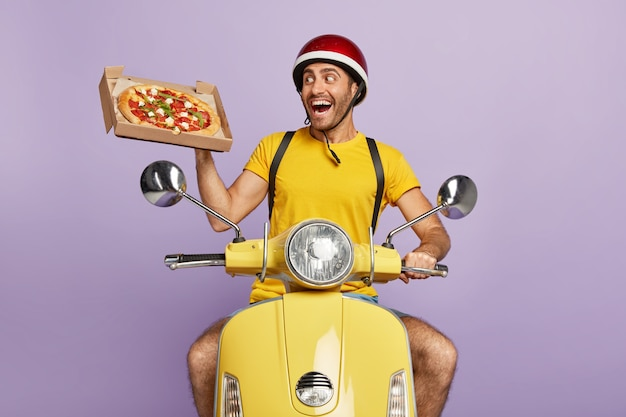 Happy deliveryman driving yellow scooter while holding pizza box
