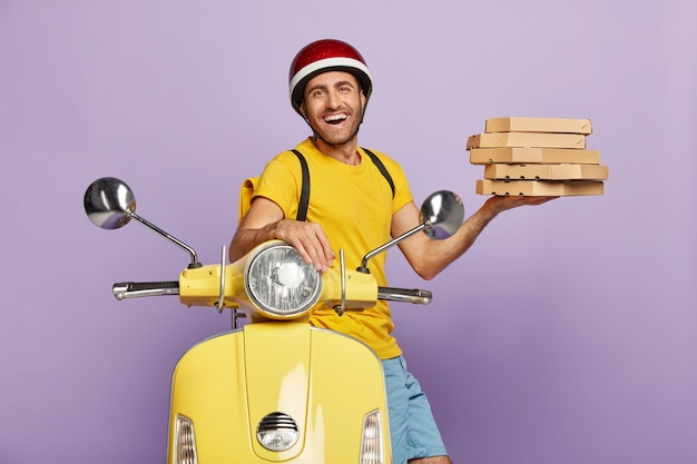 Happy deliveryman driving yellow scooter while holding pizza boxes