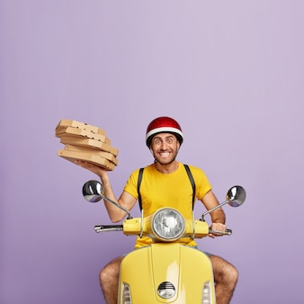 Fattorino felice alla guida di scooter giallo mentre si tengono scatole per pizza