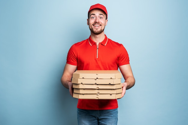 Happy deliveryman happy to delivers pizza with success. cyan background