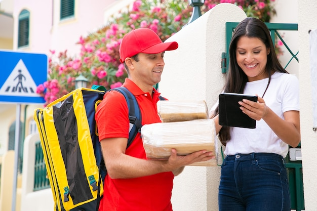 태블릿 고객 근처에 서 행복 배달원입니다. 빨간색 유니폼 상자를 들고 주문을 배달하는 전문 우편 배달부. 소포를 받고 예쁜 여성 고객입니다. 배달 서비스 및 포스트 개념