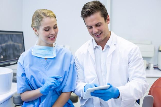 Счастливый стоматолог и медсестра с помощью цифрового планшета