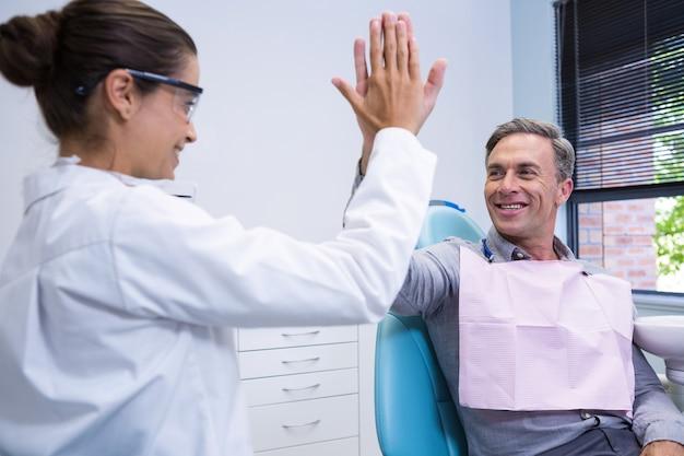 男にハイタッチを与える幸せな歯科医