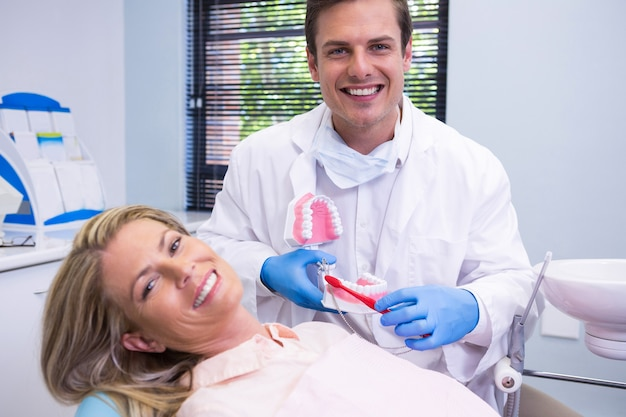 Happy dentist holding dental mould by woman at medical clinic
