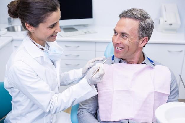 Счастливый стоматолог держит инструмент, глядя на человека