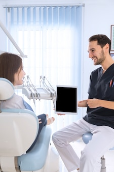 Happy dentist pointing on digital tablet screen to female patient in clinic