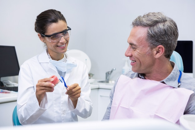 Happy dentist teaching man brushing teeth on dental mold