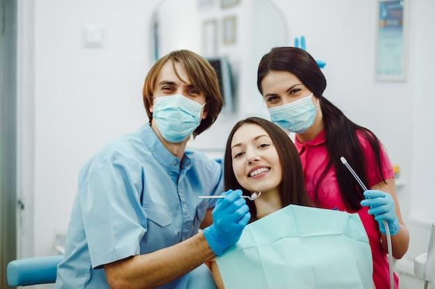 Счастливые стоматологи с пациентом