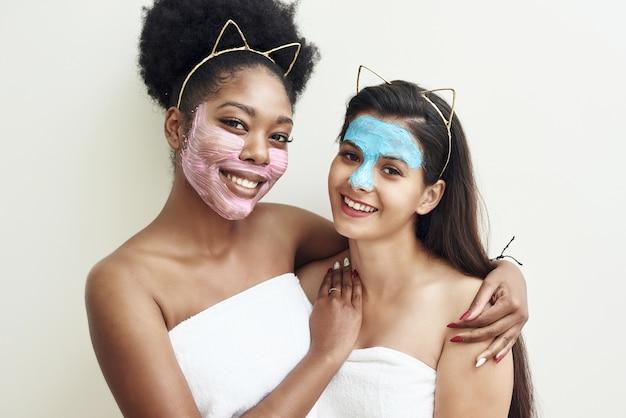 행복한 다른 젊은 여성들이 수건에 서서 웃고, 화장품 마스크로 서로 이야기합니다.