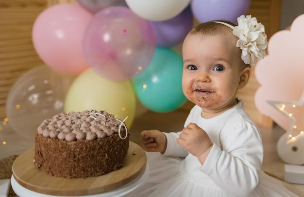 행복한 더러운 아기 소녀는 케이크를 먹고 카메라를 찾습니다
