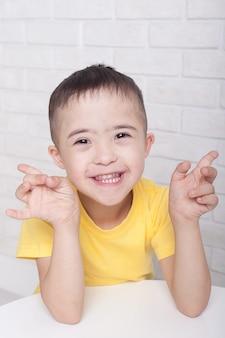 다운 증후군 웃 고 흰색 배경 위에 절연 포즈 동안 카메라를 흔들며 행복 장애인 소년. 장애 및 특수 요구 개념을 가진 어린이. 웹 배너