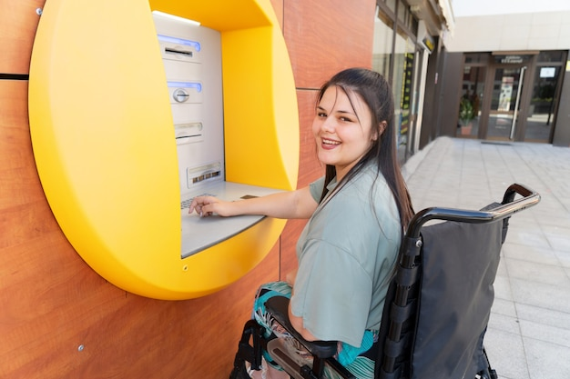 Happy disabled handicapped woman in wheelchair using atm cash machine and smiling at camera on sunny summer day