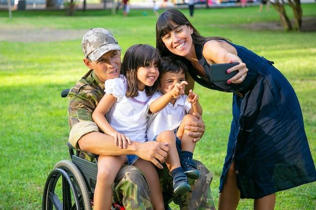 Uomo militare in pensione disabile felice che tiene i bambini in braccio mentre sua moglie prende selfie di famiglia sul cellulare. veterano di guerra o concetto di ritorno a casa