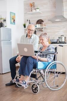 キッチンでのビデオ会議中に幸せな障害のある女性。車椅子の障害者の年配の女性と彼女の夫がキッチンのタブレットpcでビデオ会議を行っています。麻痺した老婆と彼女の夫