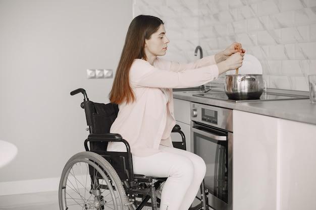 キッチンで食事を準備している車椅子の幸せな障害のある女性。