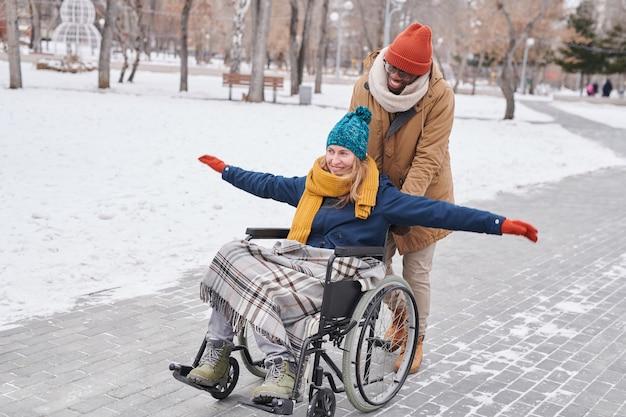Счастливая женщина-инвалид, сидящая в инвалидной коляске и веселящаяся вместе со своим другом на открытом воздухе