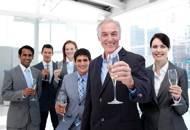 シャンパンでトーストするハッピーで多様なビジネスグループ