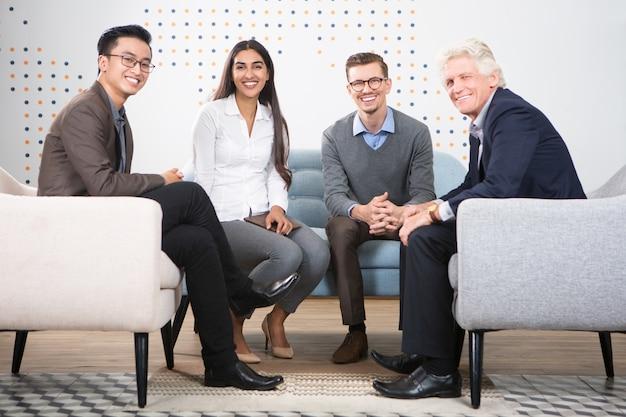 Счастливые разнообразных бизнес-партнеров, сидя в холле