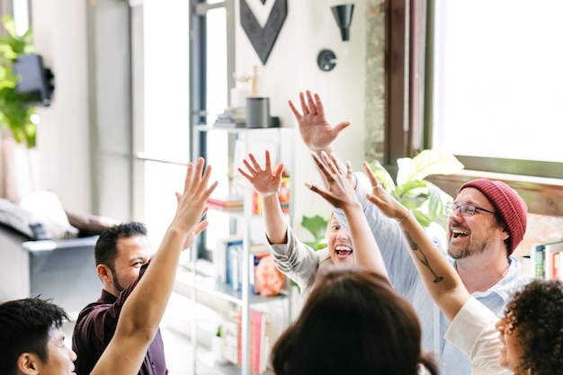 ハイタッチをしているスタートアップ企業の幸せな多様な同僚