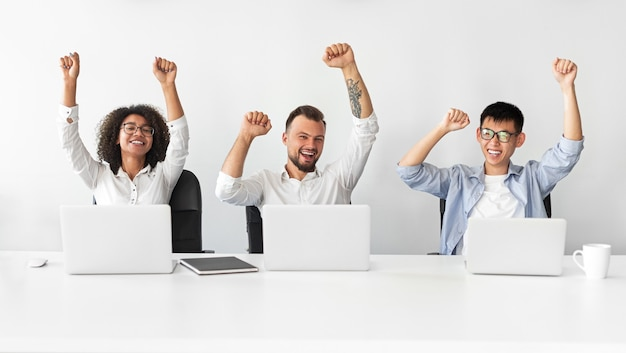 Happy diverse colleagues screaming in excitement and raising clenched fists while celebrating victory during job in office