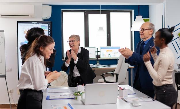 勝利を祝う新しいビジネスチャンスを持つ幸せな多様な同僚