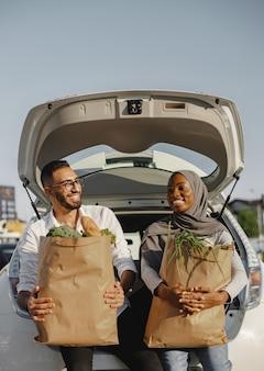 食料品の買い物の後に楽しんでいる幸せな多様なカップル。新鮮で健康的な食べ物でいっぱいの車のトランクに座っています。