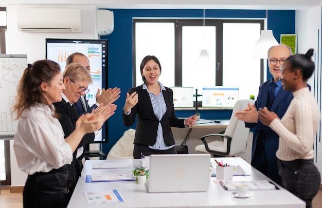 プレゼンテーションが成功した後、拍手する幸せな多様な同僚