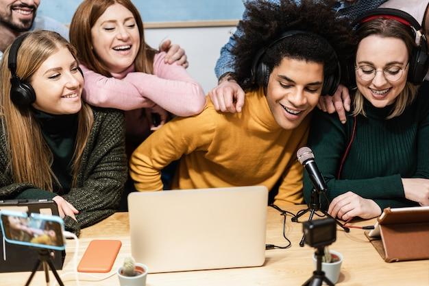 Счастливые разные друзья веселятся в потоковом режиме онлайн с помощью компьютерного ноутбука и приложения для смартфона - основное внимание уделяется лицу африканского человека