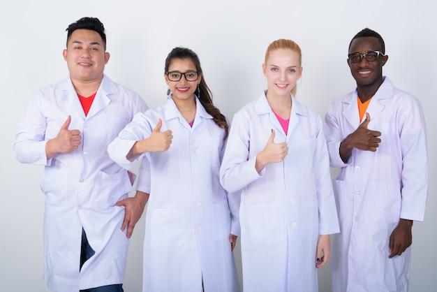 笑顔で親指を現して多民族の医師の幸せな多様なグループ