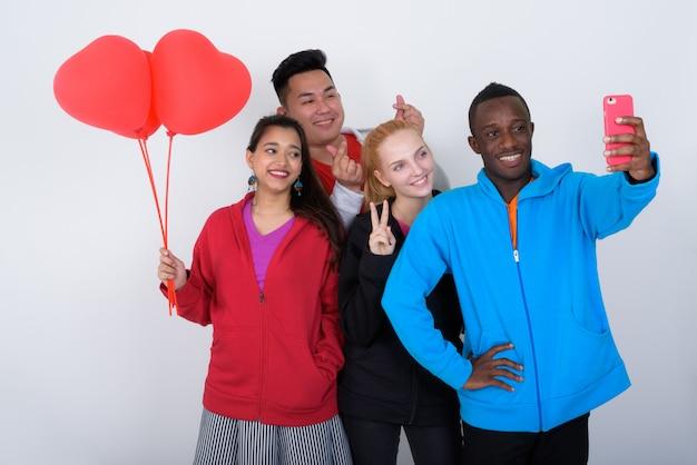 Счастливая разнообразная группа многоэтнических друзей улыбается
