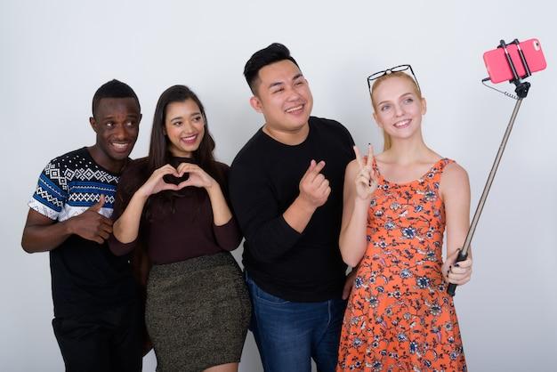 Счастливая разнообразная группа многоэтнических друзей, улыбаясь и позирующих