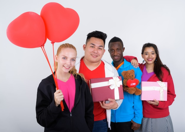 Счастливая разнообразная группа многоэтнических друзей, улыбаясь, держа