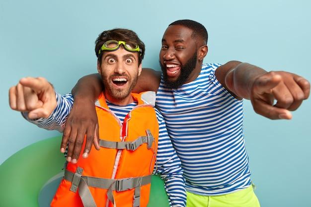 Felici ragazzi diversi abbracciano e indicano direttamente la telecamera, si divertono in spiaggia, posano con il salvagente
