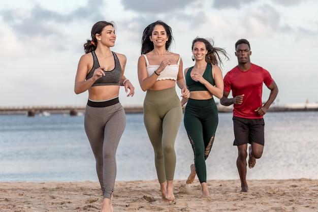Happy diverse man and women running on beach