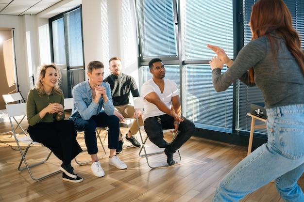 Счастливые разнообразные многонациональные офисные работники весело играют в активные игры во время тимбилдинга в современном офисе. молодая счастливая женщина играет в шарады, показывая пантомиму друзьям у окна.