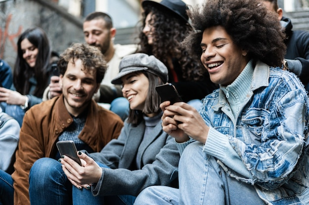 Happy diverse people using mobile phones outdoor in the city - focus on african guy face