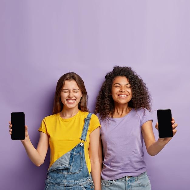 幸せな多様な姉妹が隣同士に立ち、空白の画面で携帯電話を見せ、前向きな外見を持ち、新しいガジェットを宣伝します