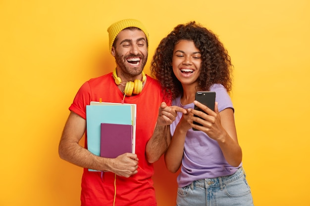Happy diverse students look happily at smartphone device, hold notepad, wear stylish bright clothes
