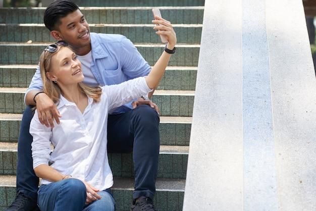 階段に座って、ソーシャルメディアに投稿するために自分撮りを取っている幸せな多様な若いカップル