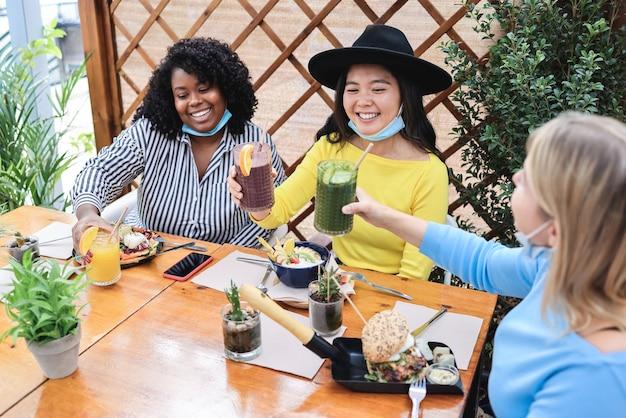 安全マスクを着用しながらブランチレストランで食べる幸せな多様な若い友人-アジアの女の子の顔に焦点を当てる
