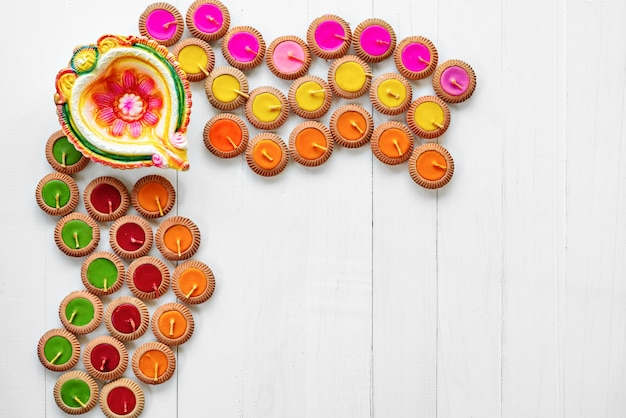 Happy diwali - clay diya lamps lit during dipavali, hindu festival of lights celebration. colorful traditional oil lamp diya on white wooden background
