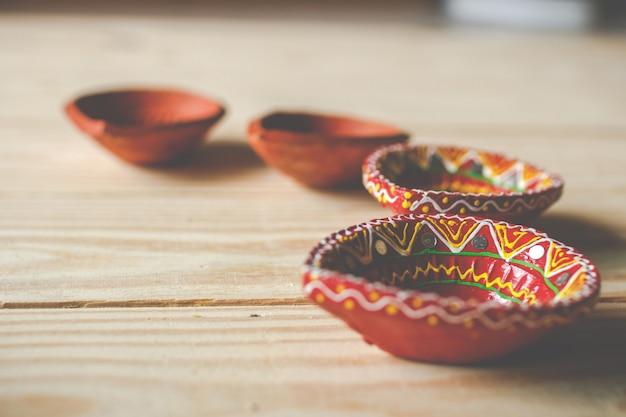 Счастливого дивали - глиняные лампы дия зажжены во время дипавали, индуистского фестиваля огней. масляная лампа дия на деревянном фоне
