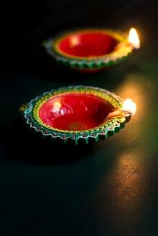 Happy diwali - clay diya lamps lit during diwali celebration. greetings card design of indian hindu light festival called diwali