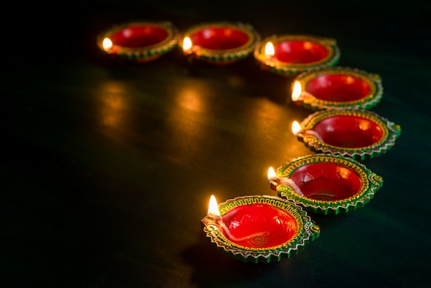 Happy diwali - clay diya lamps lit during diwali celebration. greetings card design of indian hindu light festival called diwali