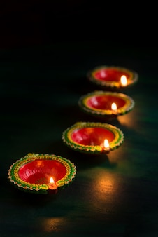 Happy diwali - diya lamps lit during diwali celebration. greetings card design of indian hindu light festival called diwali