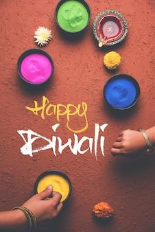 ボウルにカラフルなランゴーリー、ディワリ粘土ランプまたはディヤ、ランゴーリーを作る女の子または女の子などのディワリ祭の要素を使用してクリックした幸せなディワリのグリーティングカード