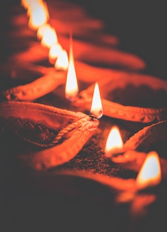 Happy diwali - many terracotta diya or oil lamps arranged over clay surface or ground in one line or curved or zigzag form, selective focus