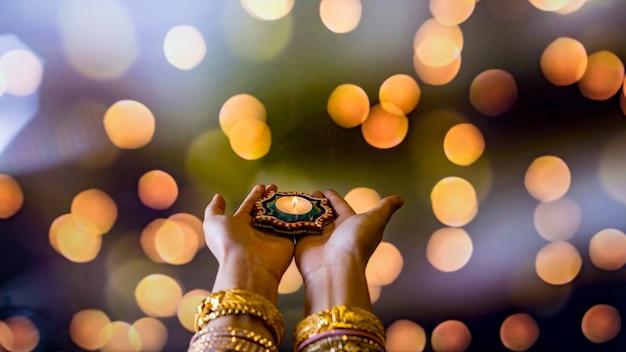 幸せなディワリ祭-暗い背景で隔離の火のともったろうそくを保持しているヘナと女性の手。クレイディヤランプは、ヒンドゥー教の光の祭典であるディパバリの間に点灯しました。テキスト用のスペースをコピーします。